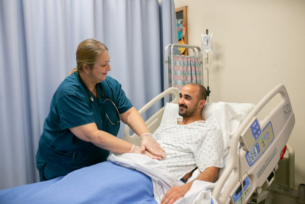 Adult student training at side of hospital bed